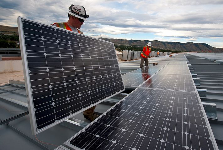 Two workers providing solar panel financing and installation